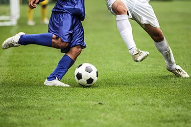 Duas pessoas jogando futebol em um campo